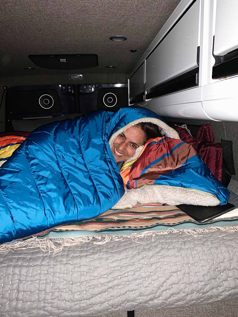 Suzy enjoys the custom mattress and bed in their custom Sprinter van